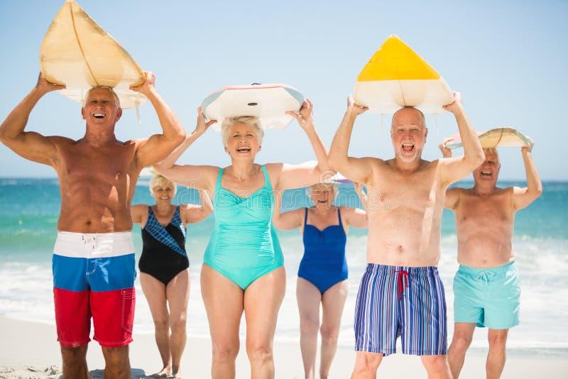 Pensionärer som rymmer surfingbrädor på stranden fotografering för bildbyråer