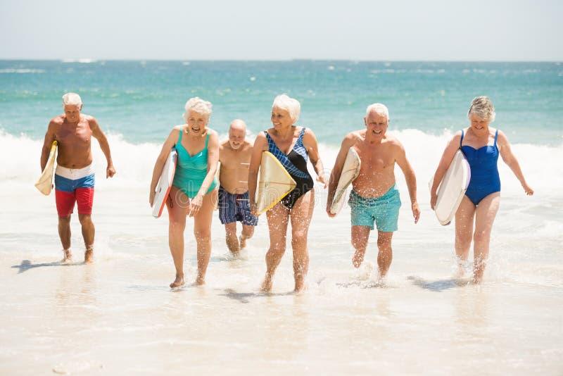 Pensionärer som rymmer surfingbrädor på stranden arkivbild