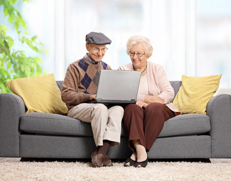 Pensionärer som sitter på en soffa och använder en bärbar dator fotografering för bildbyråer