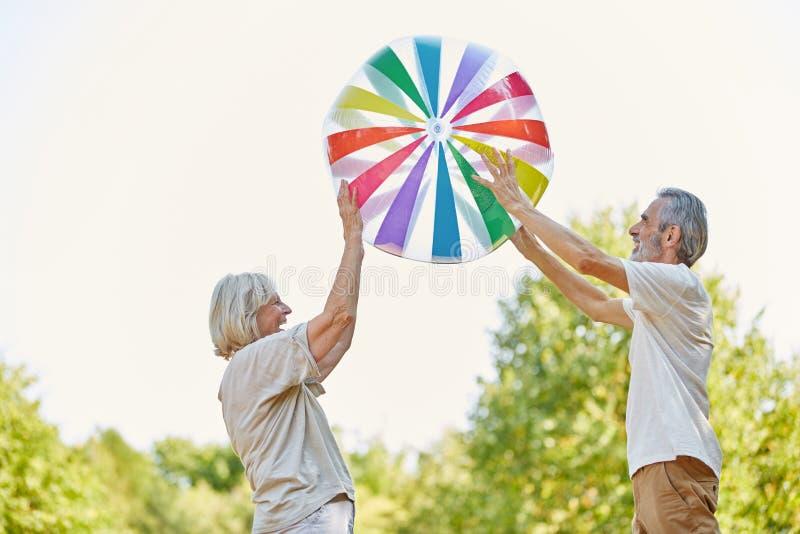 Pensionärer som spelar med en stor boll arkivbild