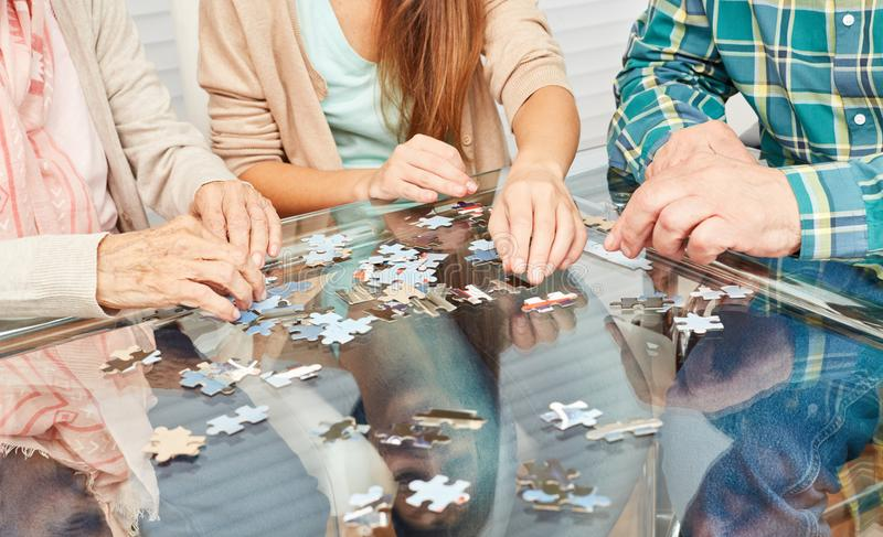 Pensionärer som spelar pusslet som demensförhindrande royaltyfri bild