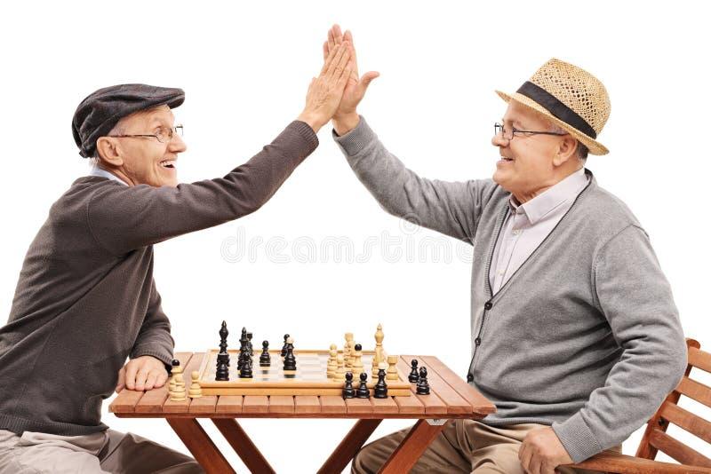 Pensionärer som spelar schack, och högt-fem arkivbilder