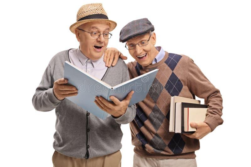 Pensionärer som tillsammans läser en bok royaltyfri bild