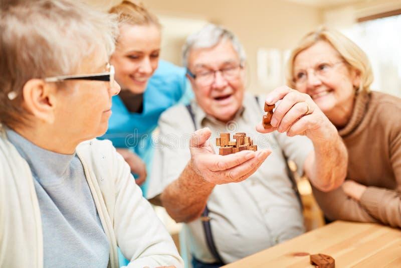 Pensionärer tycker om en lek av patiens royaltyfria bilder