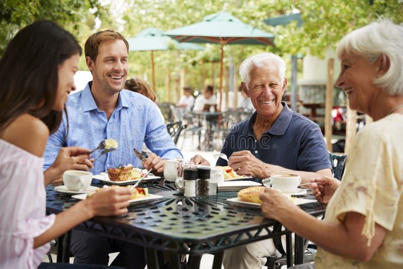 Pensionärföräldrar med vuxna barn som tycker om mål på det utomhus- kafét royaltyfri fotografi