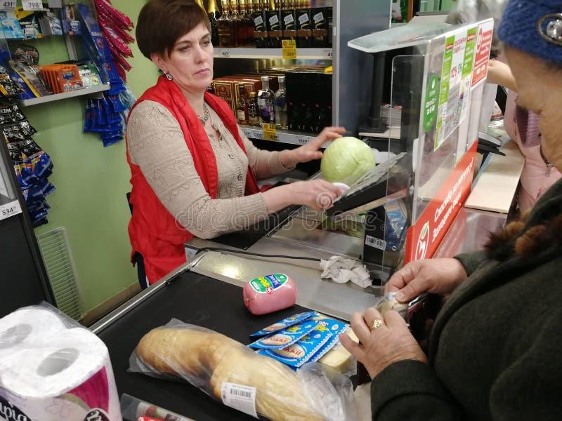 Pensionärfarmodern tar ut pengar från plånboken och betalar köpet på supermarket på checkout royaltyfri fotografi