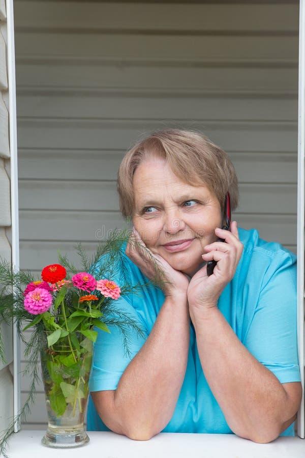 Pensionärfrau am Fenster, das telefonisch spricht lizenzfreie stockfotografie