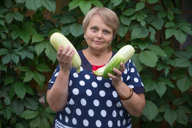 Pensionärfrau mit Kürbis im Garten stockfotografie