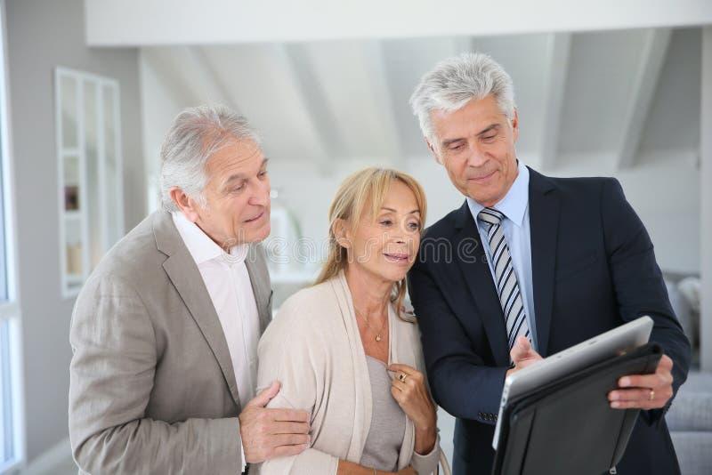 Pensionärinfallpar med fastighetsmäklaren royaltyfri foto