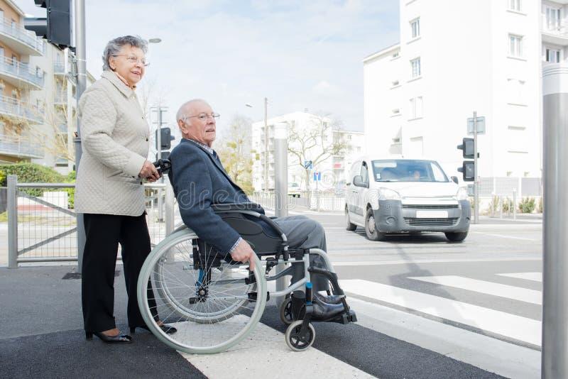 Pensionärkvinna som talar till maken i rullstol arkivfoton