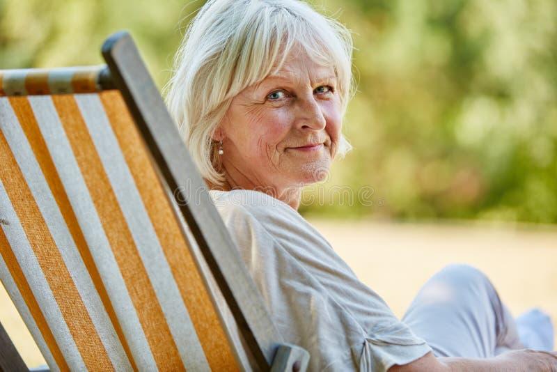Pensionärkvinnasammanträde på en solstol arkivfoton