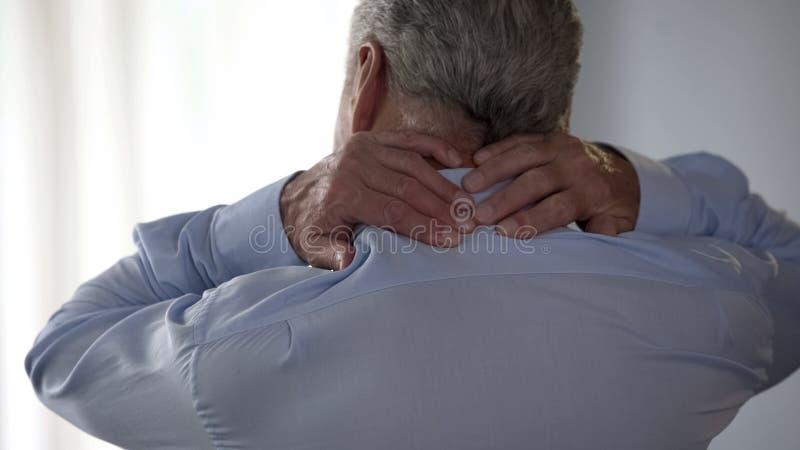 Pensionärman som tillbaka gnider av hans hals och att stå tillbaka, arbetare för kontorsskrivbord royaltyfri fotografi