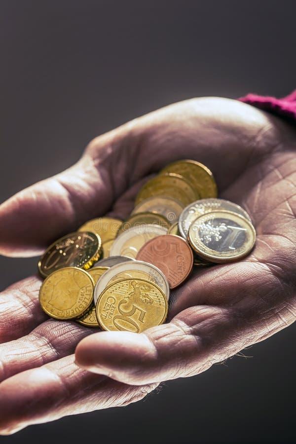 Pensionärmaninnehav i handeuromynt Tema av låga pensioner royaltyfri bild