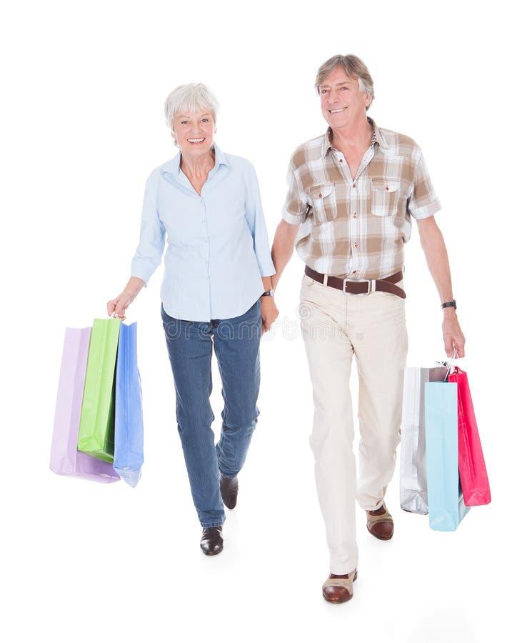 Pensionärpar som går med shoppingpåsen arkivfoton