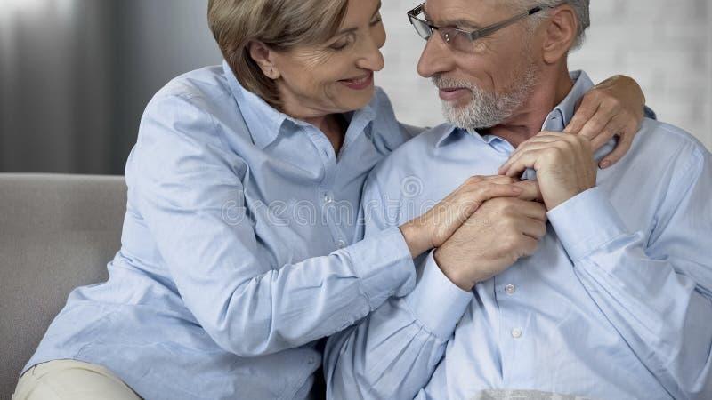 Pensionärpar som sitter på soffan, kvinnlig krama make, lyckligt äldre folk arkivbilder