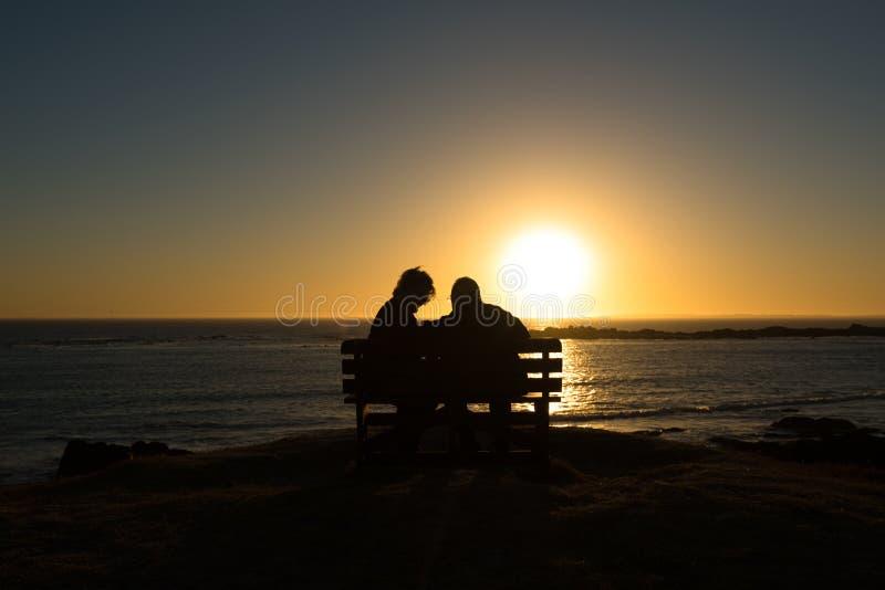 Pensionärpar som tycker om färgrik solnedgång arkivfoton