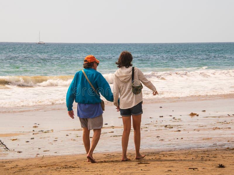 Pensionärperson född under en baby boomman och kvinnliga caucasian par som går på stranden in mot havet som rymmer händer och att royaltyfri bild