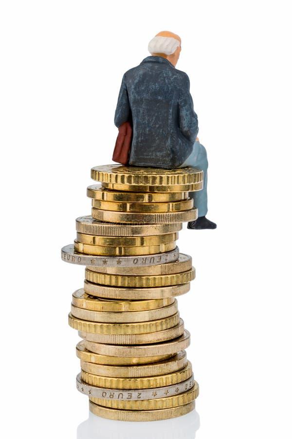 Pensionärsammanträde på en hög av pengar fotografering för bildbyråer