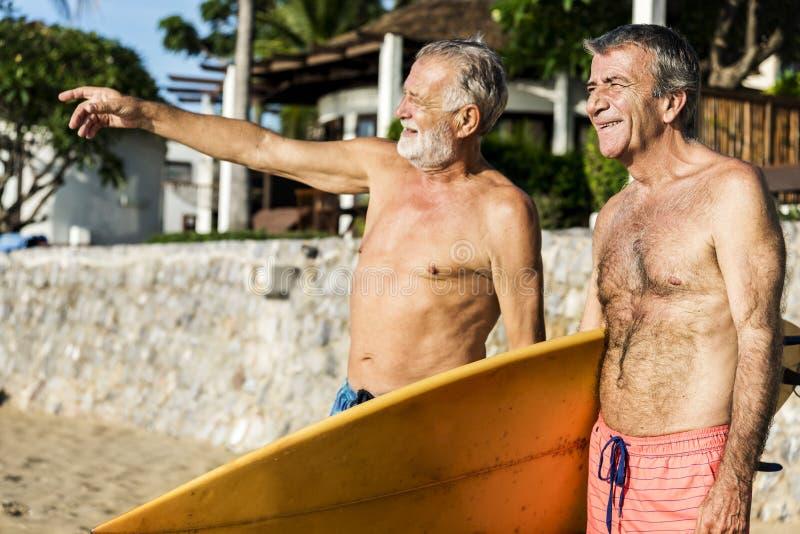 Pensionärvänner på stranden royaltyfria bilder