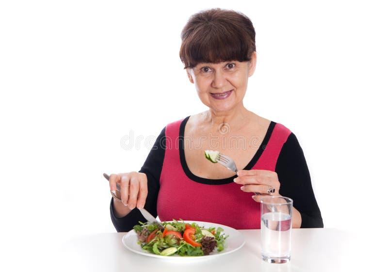 Pension age good looking smiling woman eating green salad. London, UK royalty free stock photo