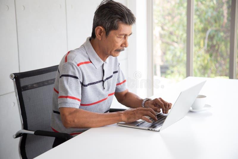 Pension?rAsien aff?rsman i tillf?lligt arbete vid bruksb?rbara datorn royaltyfri fotografi