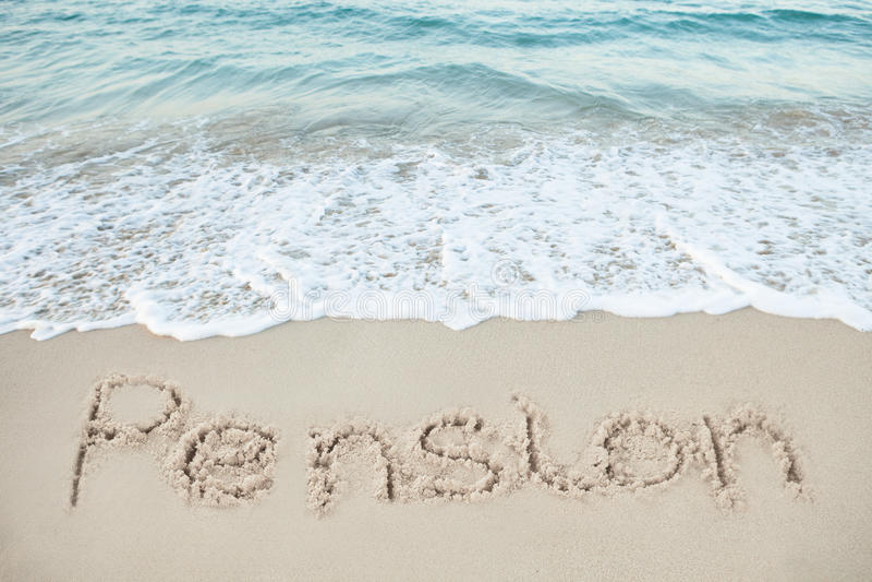Pension som är skriftlig på sand vid havet royaltyfria foton