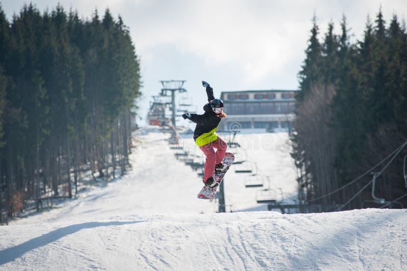 Pensionante femminile sullo snowboard che salta sopra il pendio immagine stock