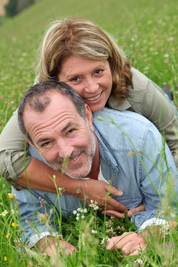 Pensionati allegri che si rilassano nell'erba fotografie stock
