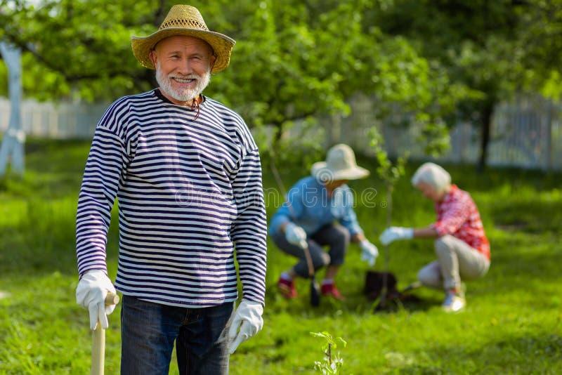 Pensionato bello che sorride mentre lavorando nel giardino immagine stock