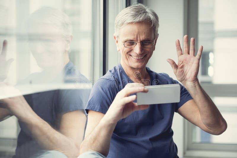 Pensionato contento che fa video chiamata fotografia stock libera da diritti