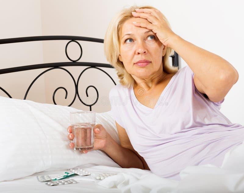 Pensionato femminile che prende medicina immagini stock