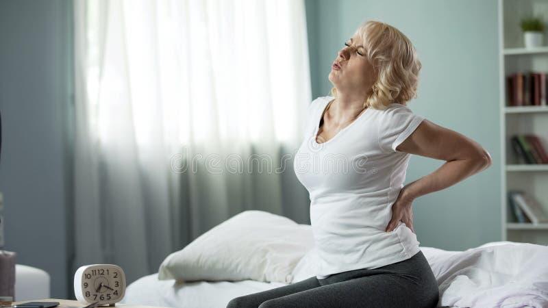 Pensionato femminile che tocca la sua parte posteriore, soffrente dal dolore, sintomo di reumatismo fotografia stock