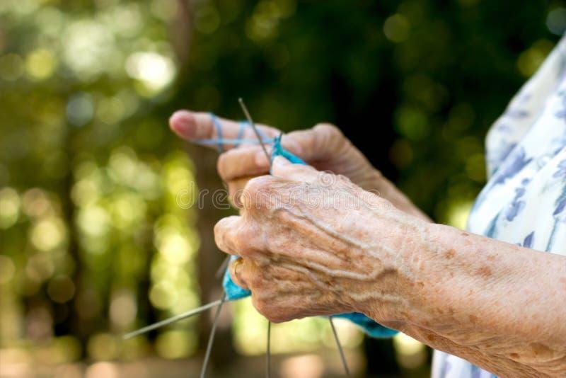 Pensionato - la donna del pensionato passa il suo tempo libero nel tricottare i calzini per i suoi nipoti, concetto di stile di v immagine stock libera da diritti