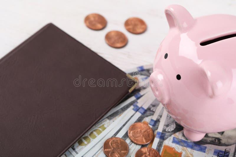 Pensioncertifikat med amerikanska pengar och piggybank på träbakgrund arkivbild