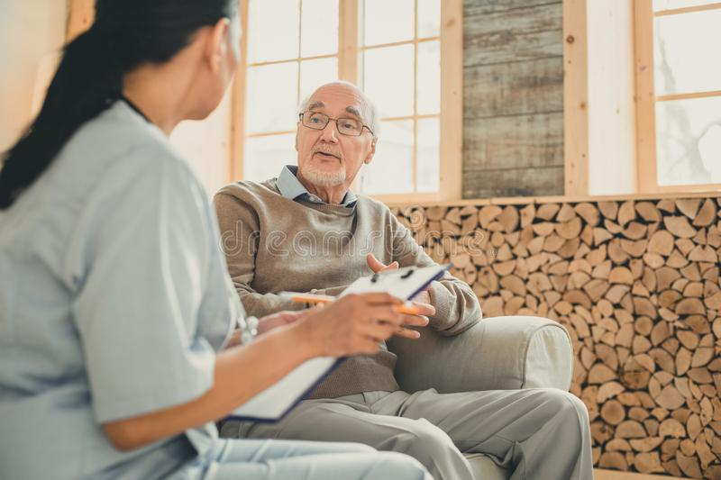 Pensioner with grey hair sitting on the couch with his doctor. Doctor with stethoscope. Pensioner with grey hair sitting on the couch with his doctor in the royalty free stock photos