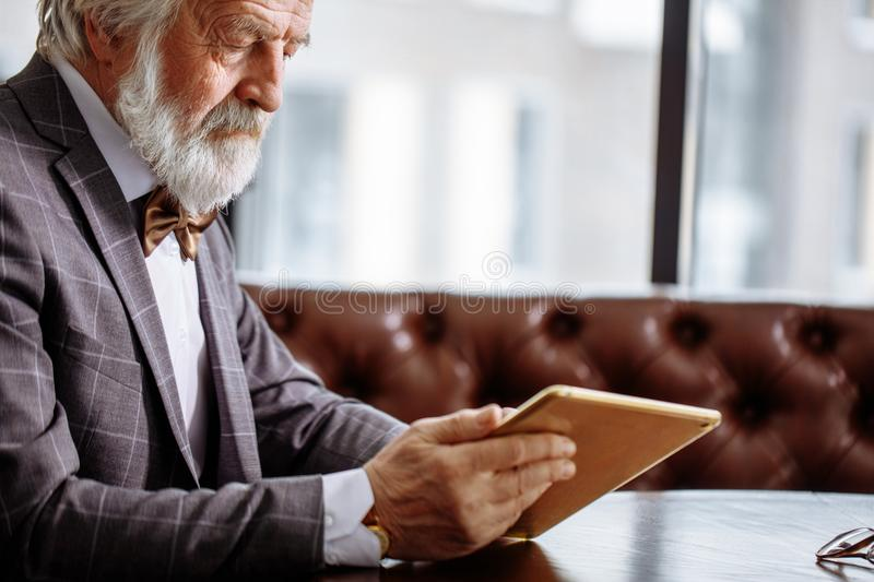 Pensioner in grey suit is lookig at the photos on tablet royalty free stock image