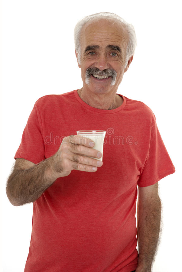 Pensioner holding glass of milk stock photography