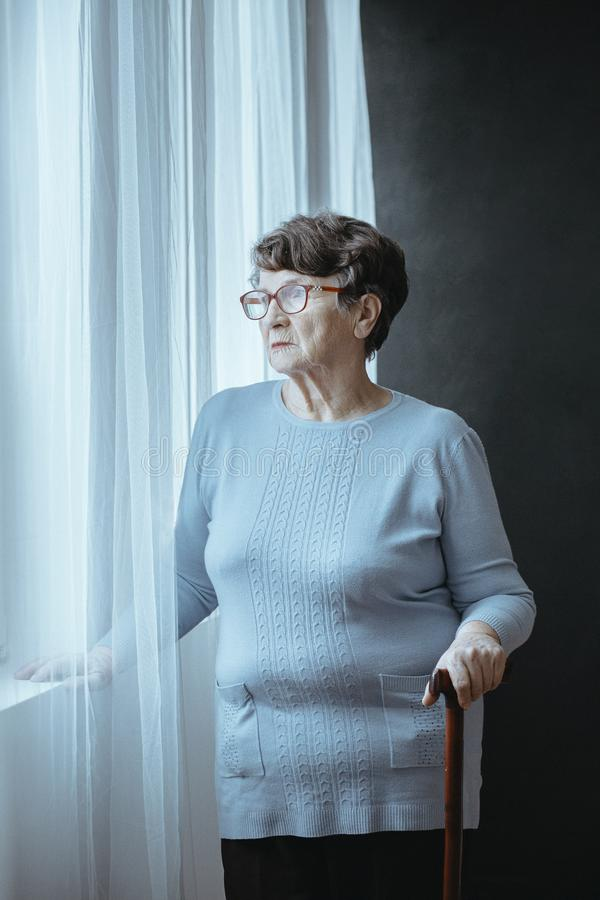 Pensioner in nursing house. Pensioner with parkinson holding wooden cane and spending time alone in nursing house royalty free stock photo