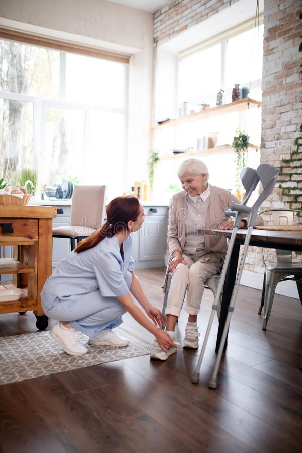 Free Pensioner Smiling While Caregiver Lacing Shoes For Her Royalty Free Stock Image - 160042186