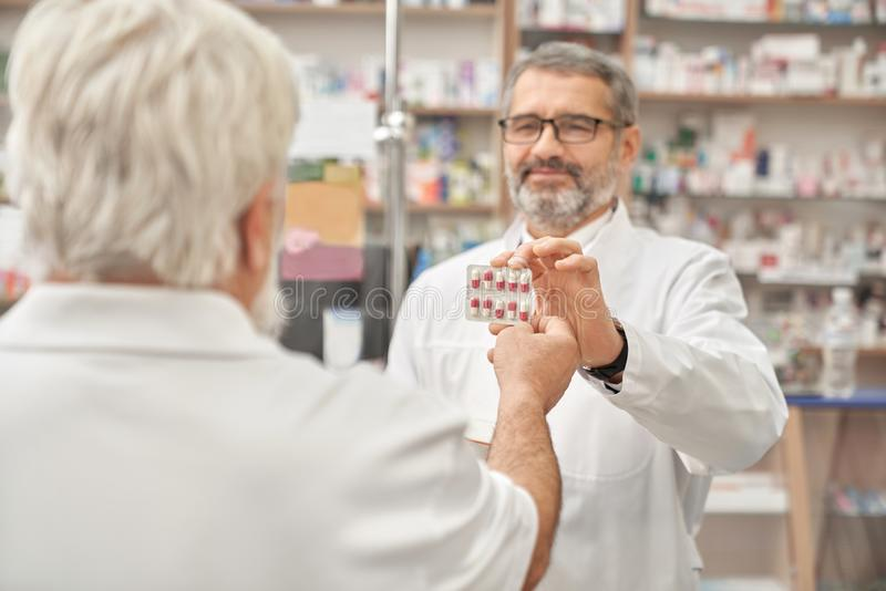 Pensioner taking blister pack from pharmacist. royalty free stock photography