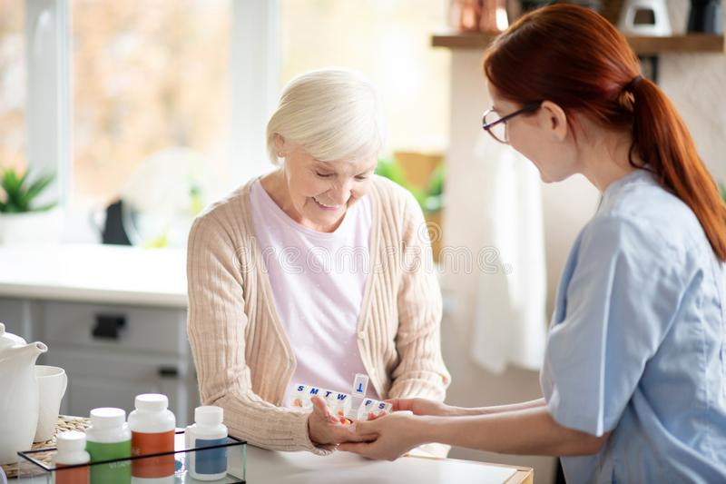 Pensioner taking vitamins standing near caregiver. Pensioner smiling. Beaming pensioner smiling while taking vitamins standing near caregiver stock image