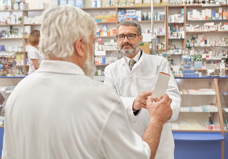 Doctor talking with elderly man in drugstore. royalty free stock images
