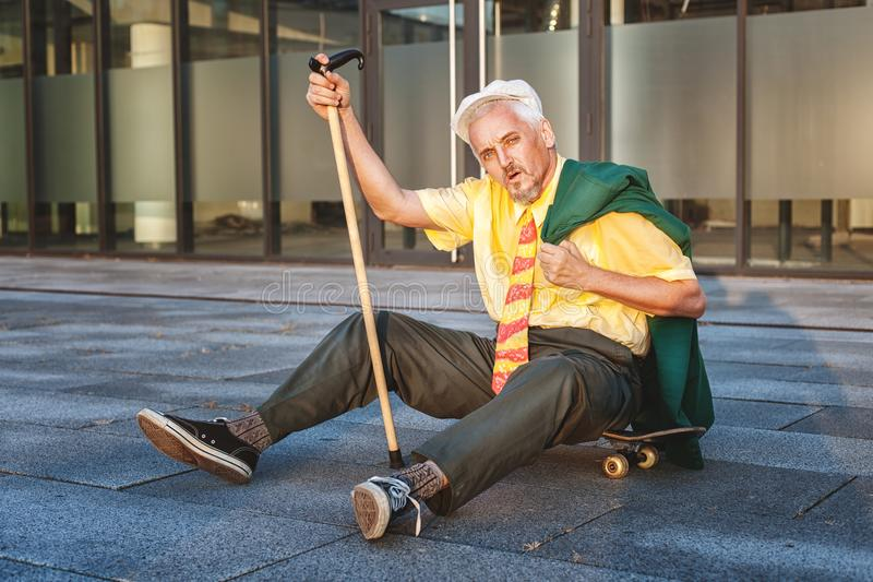 Pensioner is tiredly sitting on the skateboard. royalty free stock images