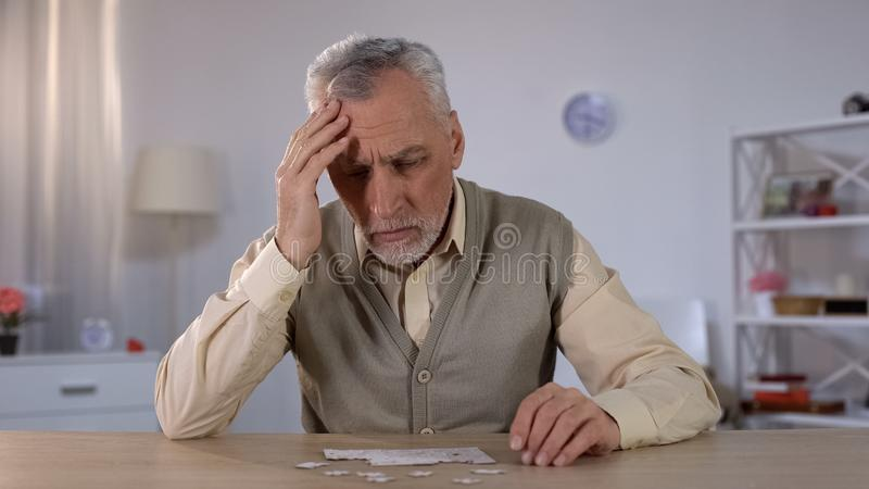 Pensioner trying to combine puzzle, having memory problems, cognitive impairment. Stock photo stock image