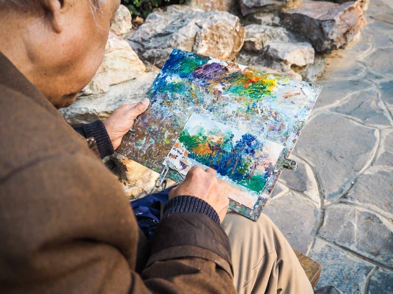 Pensionerad asiatisk man som målar en tempel för traditionell kines royaltyfria foton