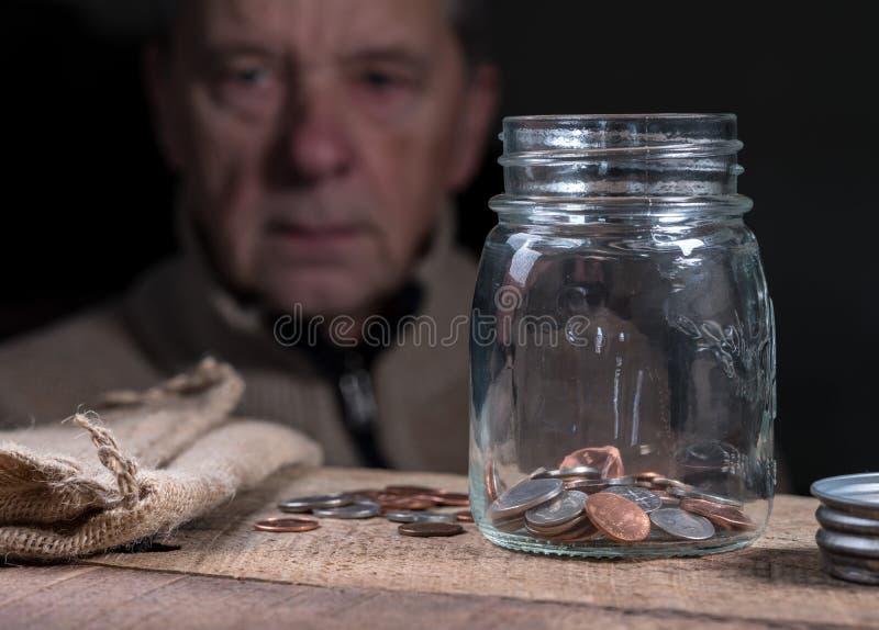 Pensionerad caucasian man för pensionär som ser resterande besparingar arkivbild