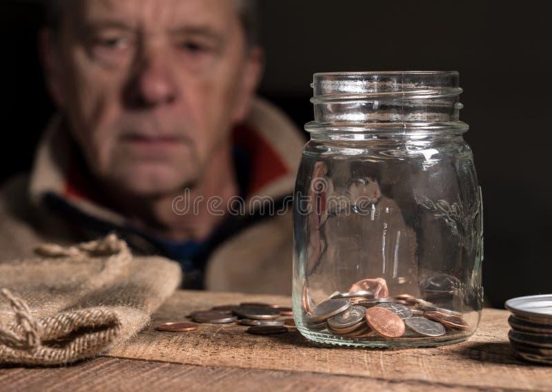 Pensionerad caucasian man för pensionär som ser resterande besparingar royaltyfria bilder