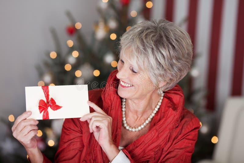 Pensionerad dam med en julpresentkort arkivfoton