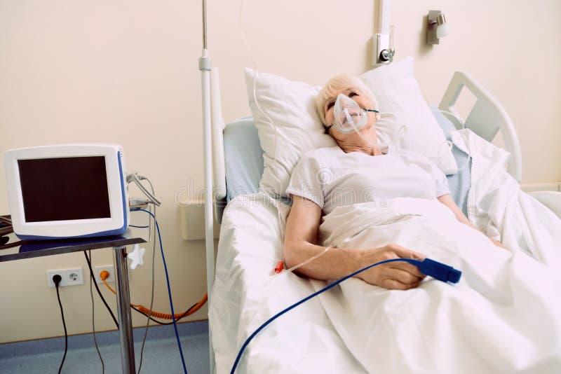Pensionerad dam som ligger i sjukhussäng med respiratorisk service arkivbilder