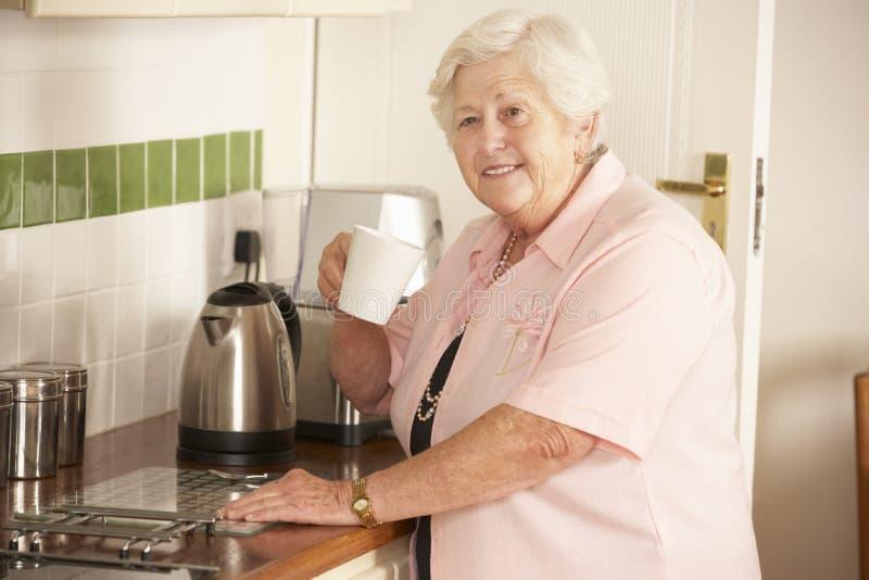 Pensionerad hög kvinna i kök som gör den varma drinken fotografering för bildbyråer
